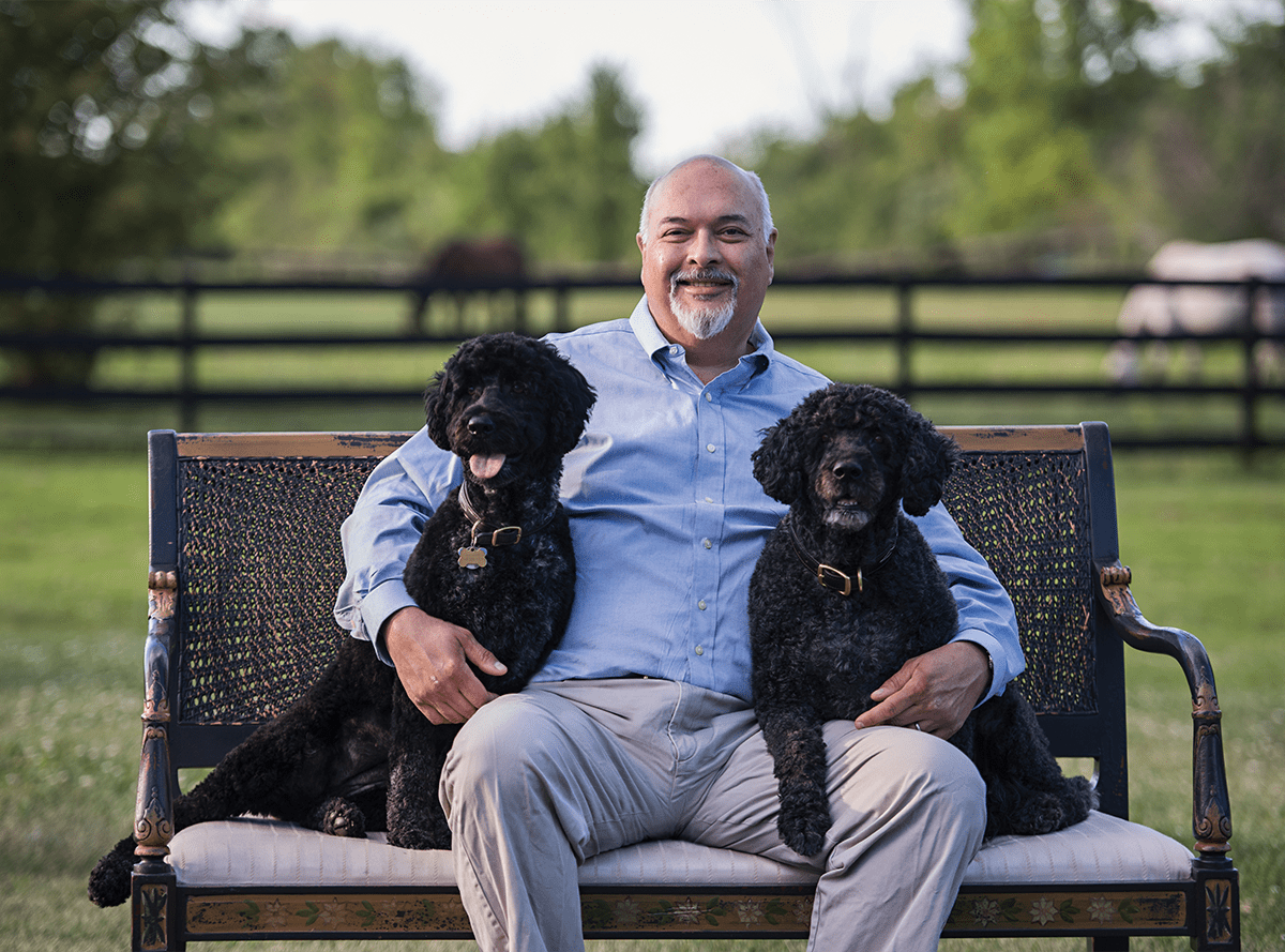 Dr. Mike Petty on a bench with 2 dogs: Animal Hospital in Canton